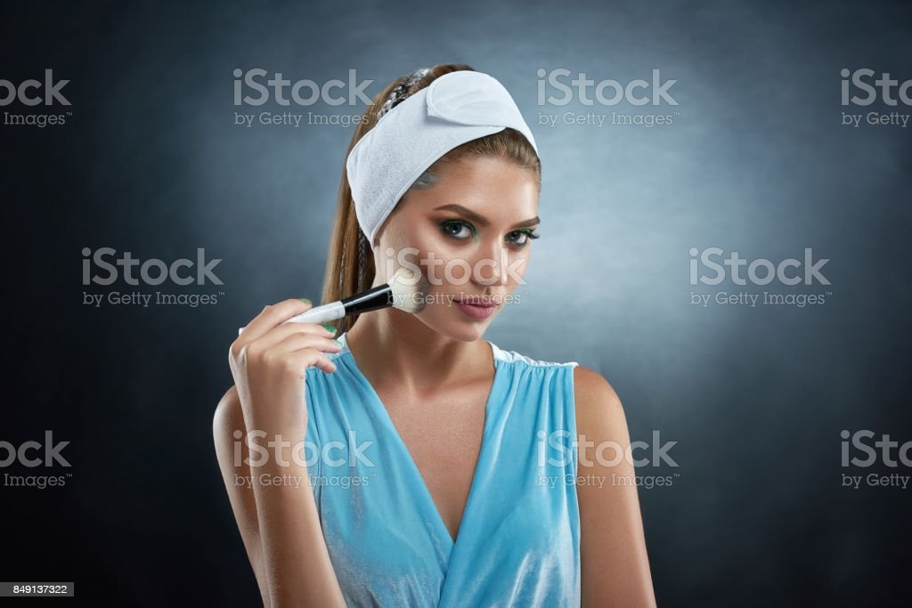 Pretty woman holding ankle and drawing blush for herself. stock photo
