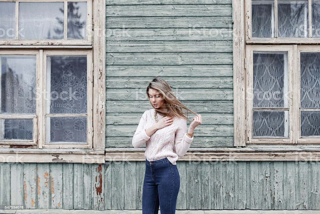 Pretty woman in a knitted sweater near wooden house stock photo
