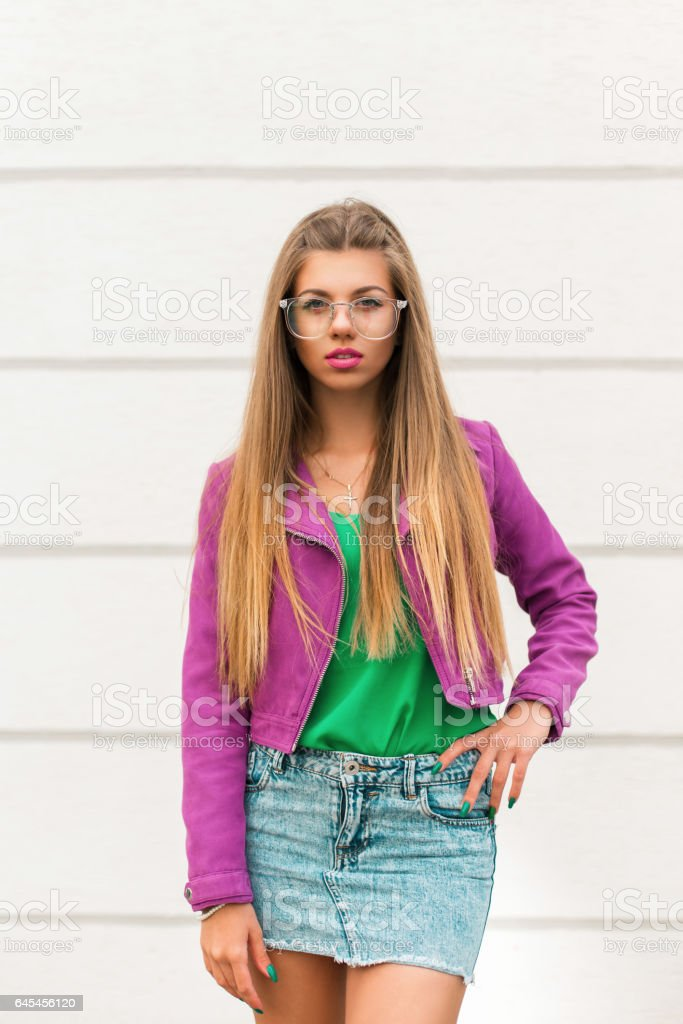 Pretty woman in fashionable sunglasses and a pink jacket and skirt is posing near a white wall stock photo
