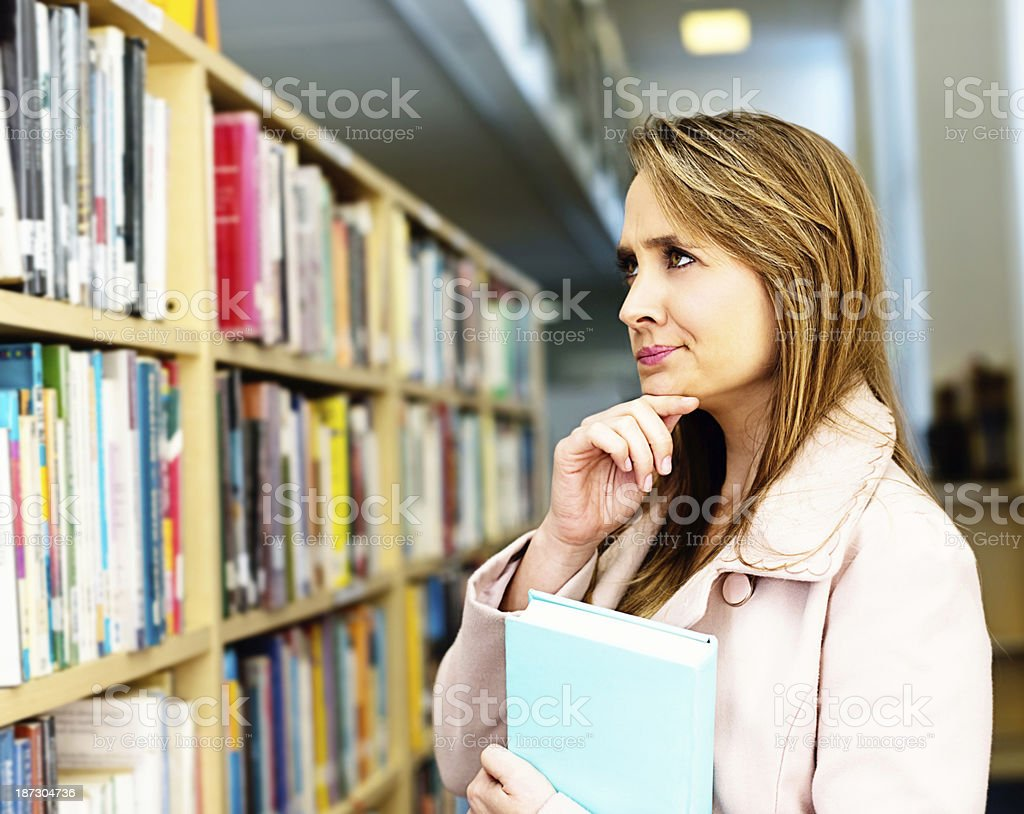 Pretty woman in library has lots to choose from! royalty-free stock photo