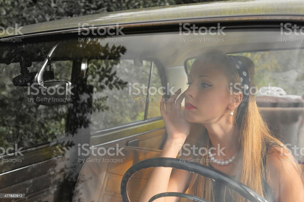 Pretty woman in old car stock photo