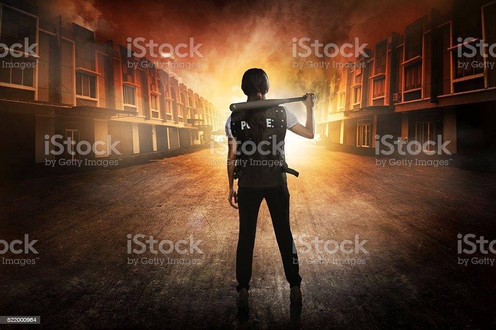 Pretty woman in police vest holding baseball bat stock photo