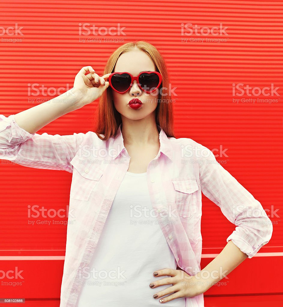 Pretty woman in red sunglasses blowing lips kiss over colorful stock photo