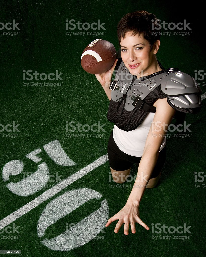 Pretty Woman in Shoulder Pads Posing to Make Forward Pass stock photo