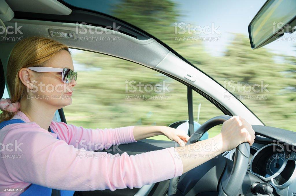 Pretty woman in sunglasses driving fast car stock photo
