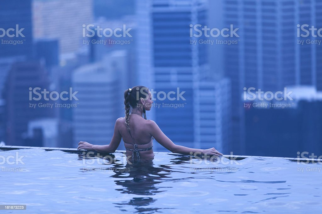 Pretty woman in swimming pool looking out over cityscape stock photo