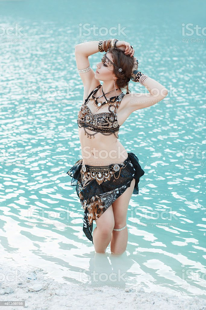 Pretty woman in tribal style on blue water stock photo