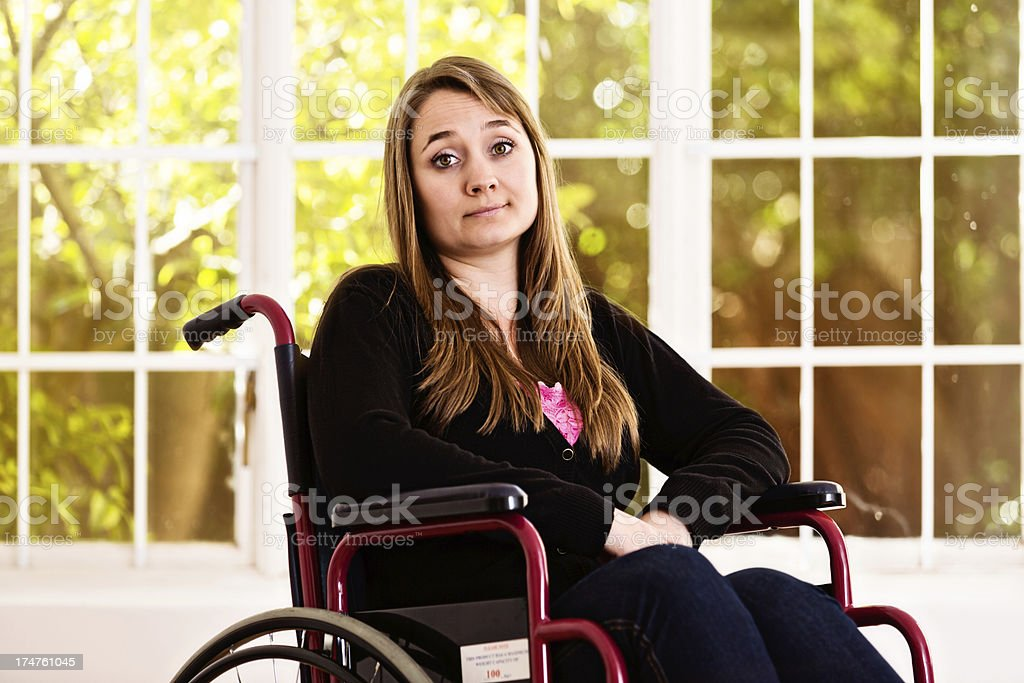 Pretty woman in wheelchair bored and frustrated by her condition stock photo