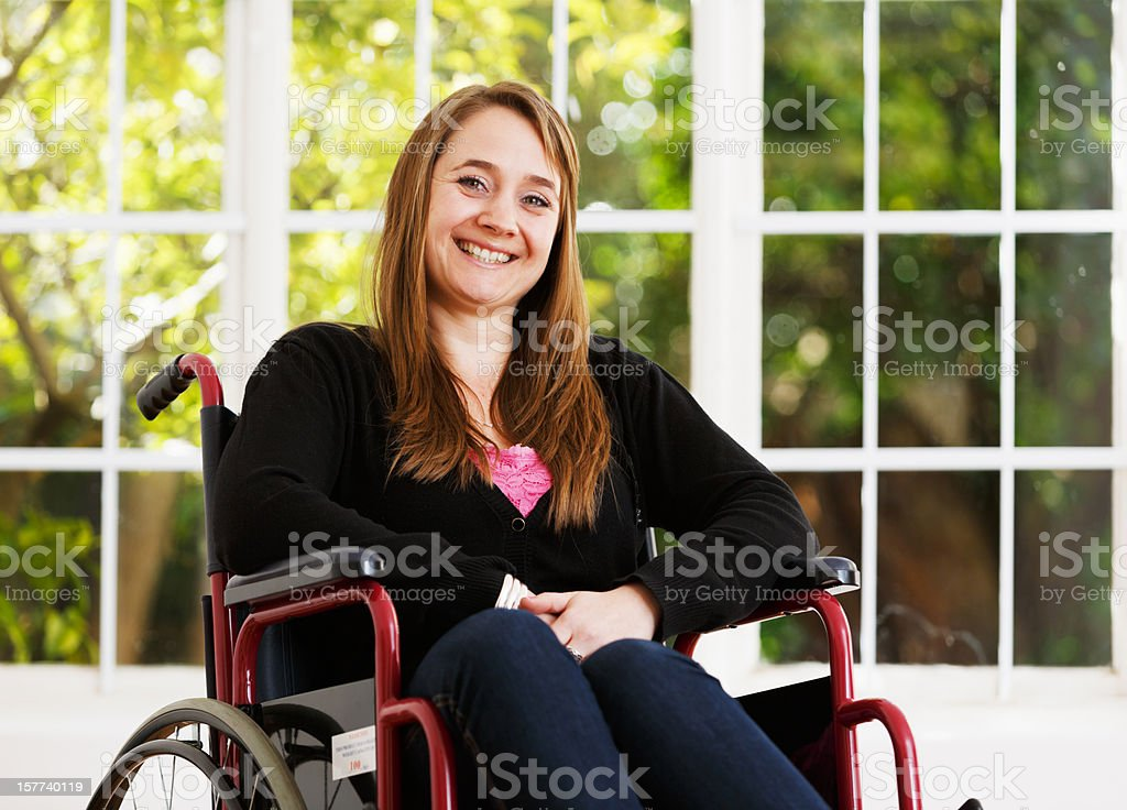 Pretty woman in wheelchair smiles bravely, overcoming adversity stock photo