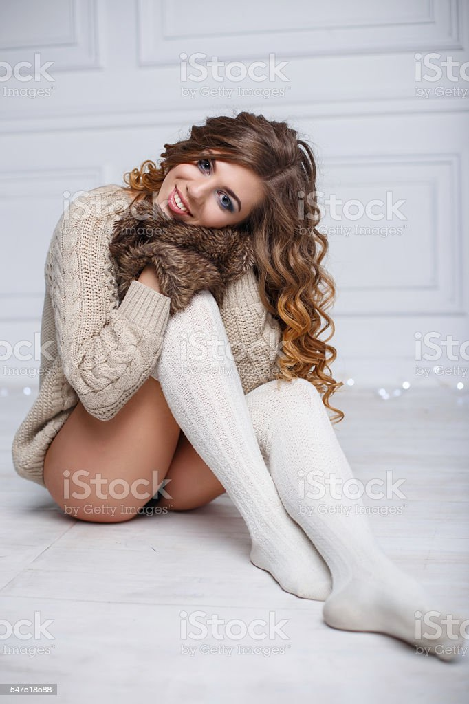 Pretty woman in winter mittens sitting on the floor stock photo