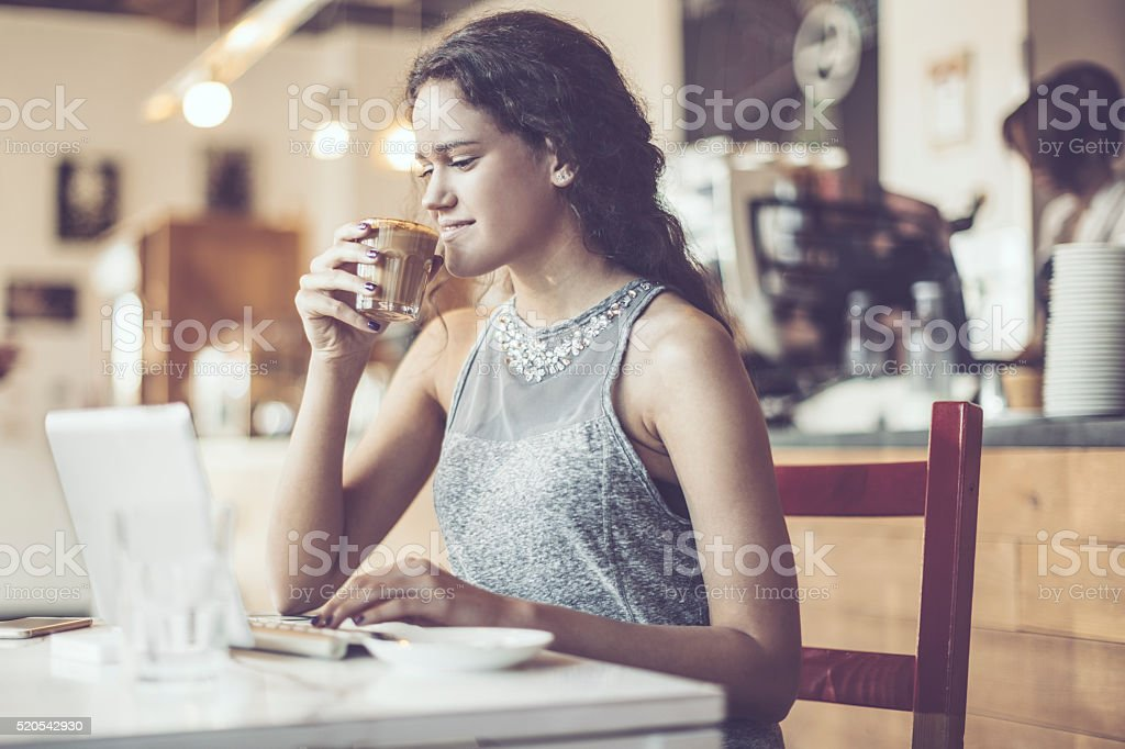 Pretty woman is enjoying a cup of coffee stock photo