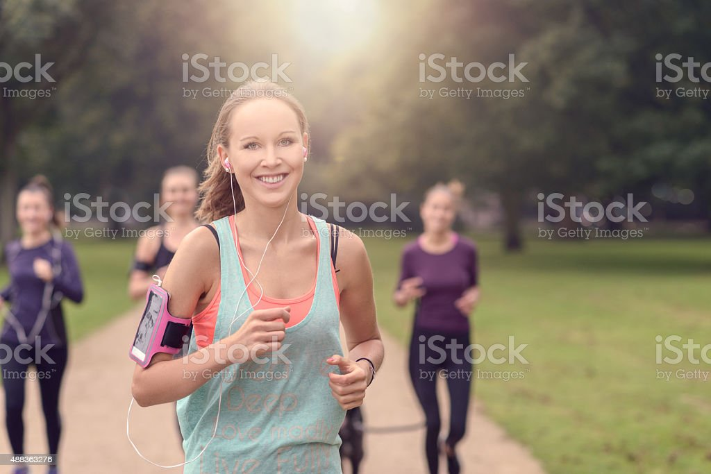 Pretty Woman Jogs in the Park with Other Girls stock photo