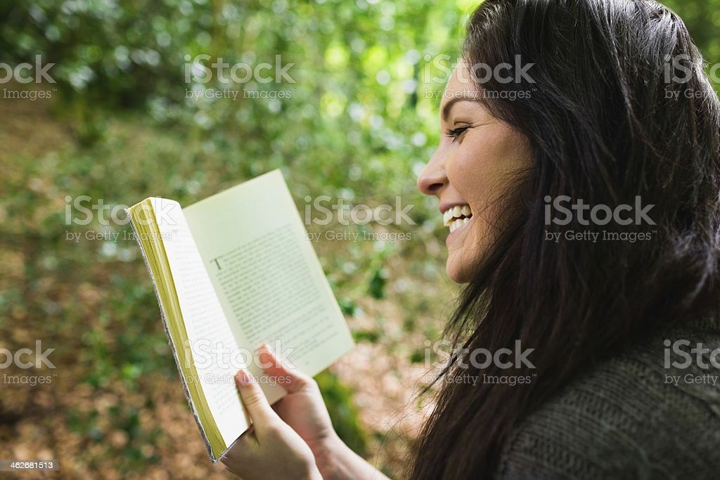 Pretty woman laughing while reading a book royalty-free stock photo