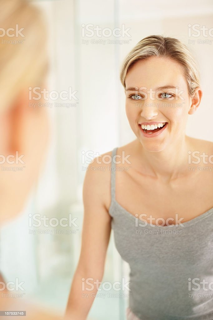 Pretty woman looking at herself in the mirror royalty-free stock photo