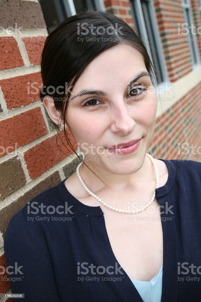 Pretty Woman Looking Forward in front of brick building royalty-free stock photo