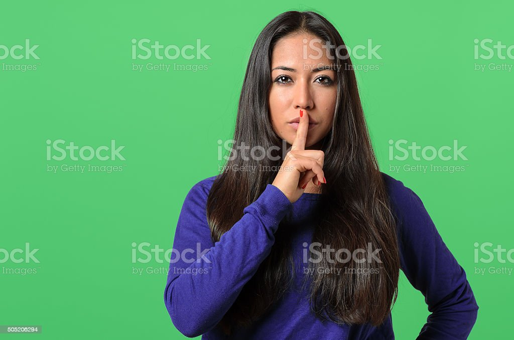 Pretty woman making a shushing gesture stock photo