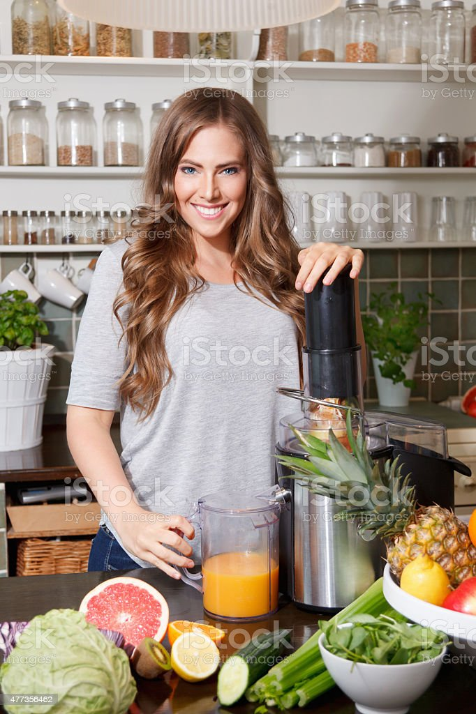 Pretty woman making healthy juice stock photo