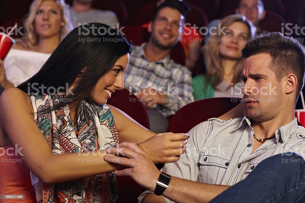 Pretty woman molesting young man at cinema stock photo