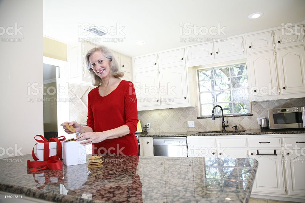 Pretty Woman Placing Cookies into Gift Box royalty-free stock photo