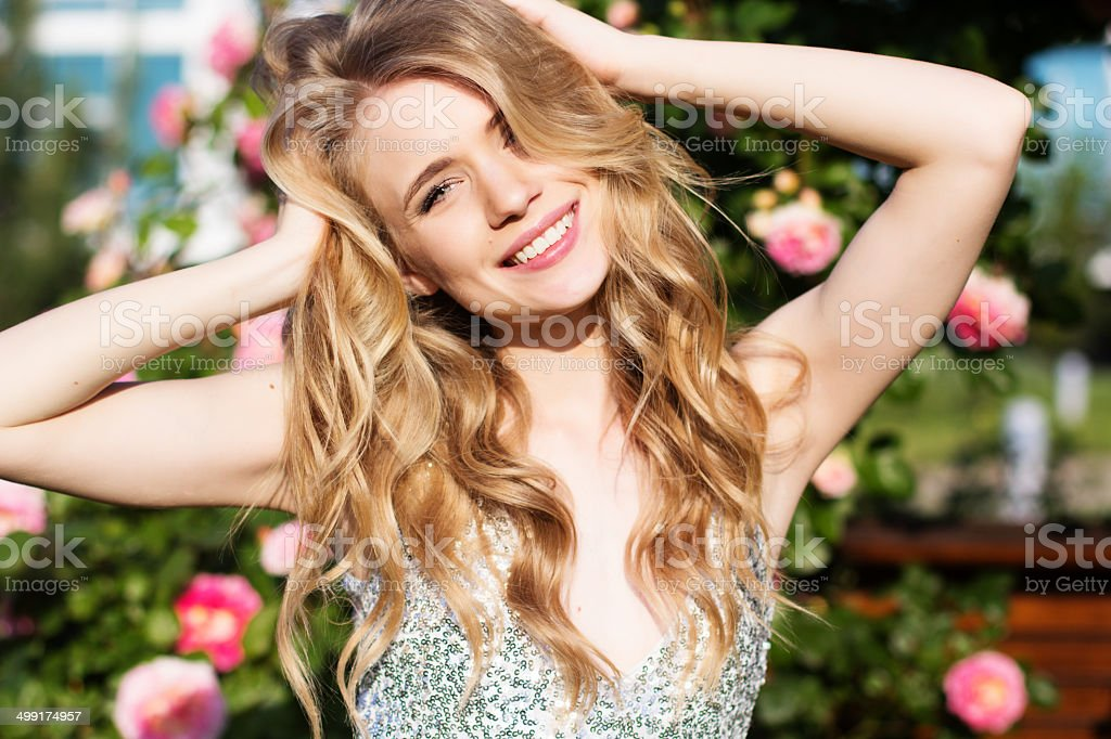 Pretty woman poses in front of flowery background stock photo