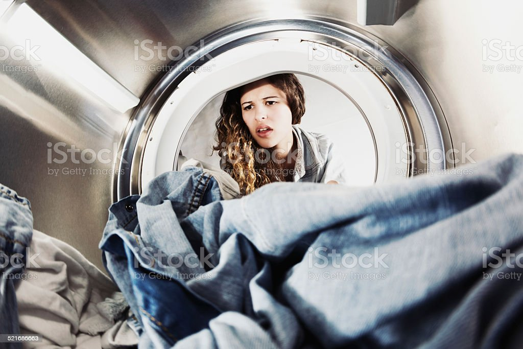 Pretty woman pulling face at laundry in drier stock photo