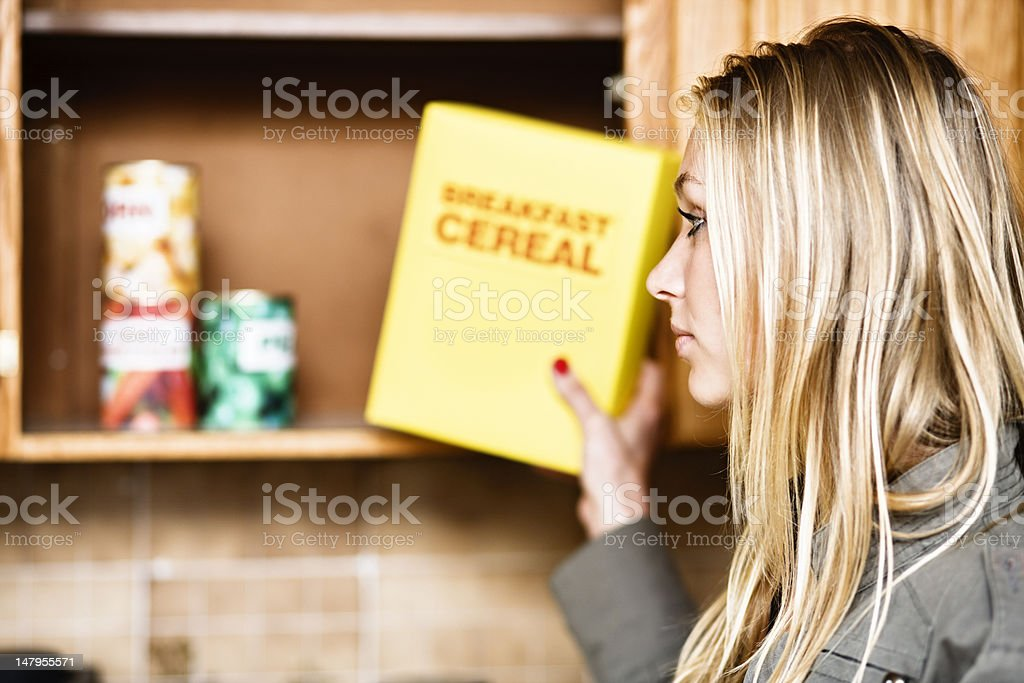 Pretty woman puts cereal away - or takes it out! stock photo