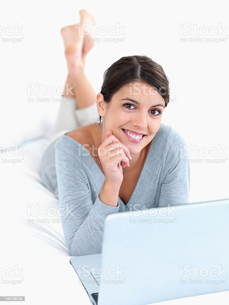 Pretty woman relaxing on bed in front of the laptop royalty-free stock photo