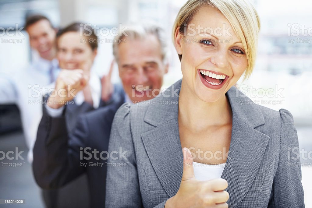Pretty woman showing thumbs up sign with team in background stock photo