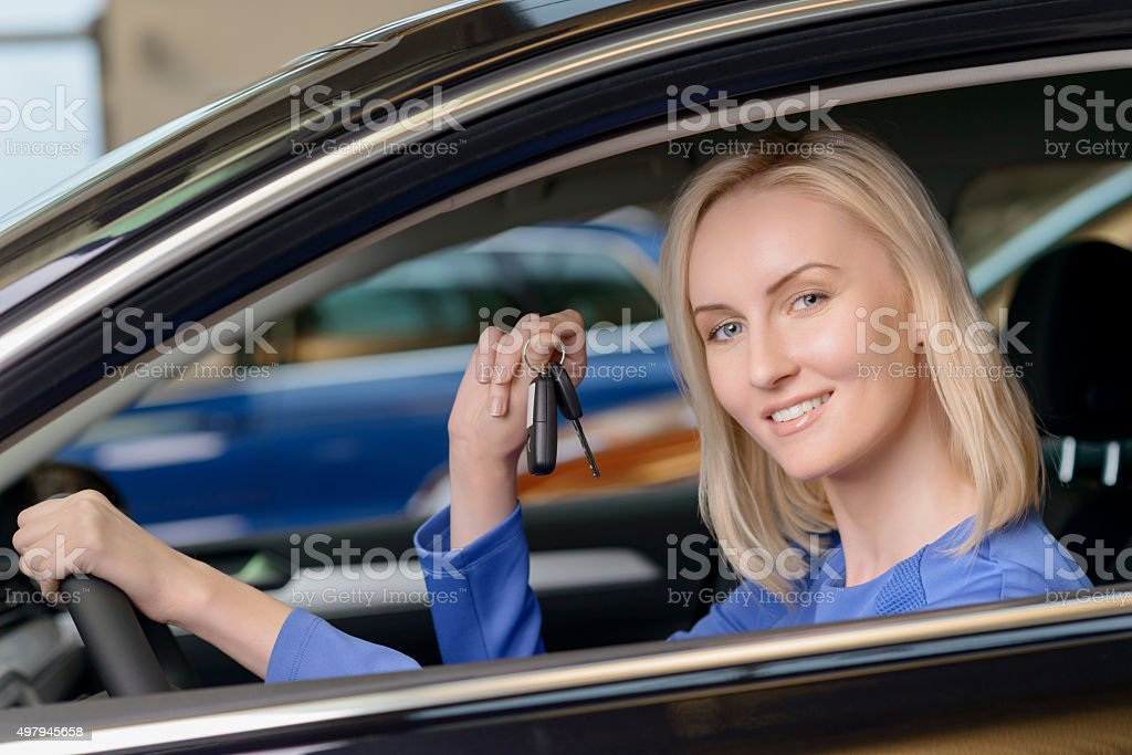 Pretty woman sitting inside her brand new vehicle stock photo