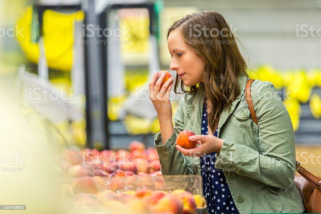 Pretty woman smelling fresh fruit stock photo