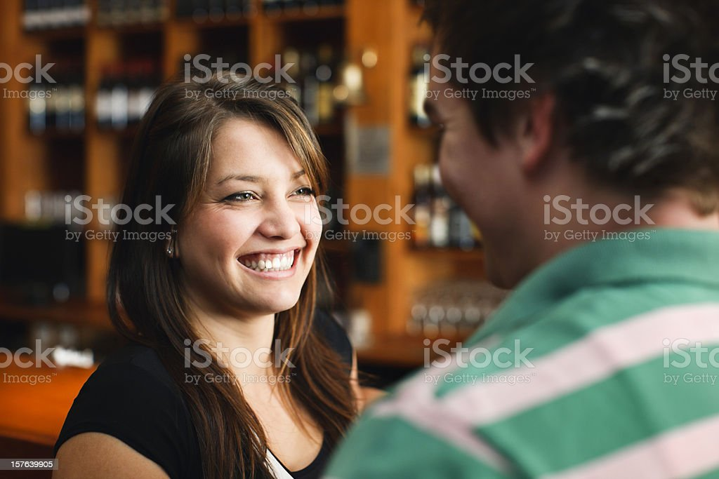 Pretty woman smiles at man in stylish bar royalty-free stock photo