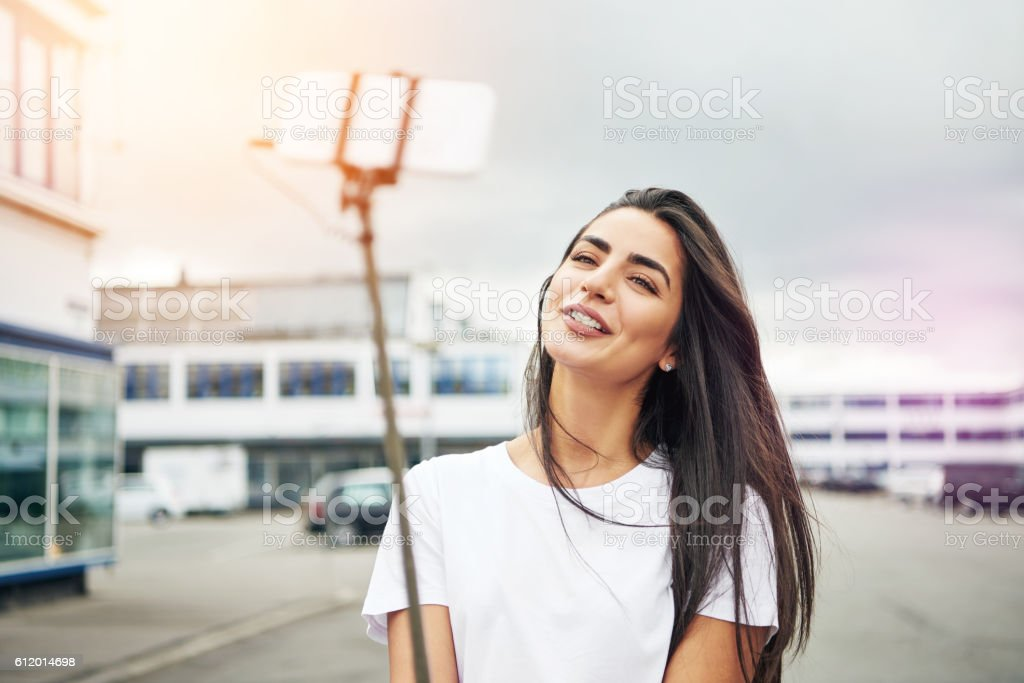 Pretty woman smiling for camera on stick stock photo