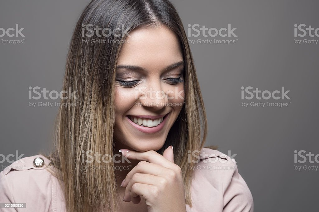 Pretty woman smiling with closed eyes with hand on ching stock photo