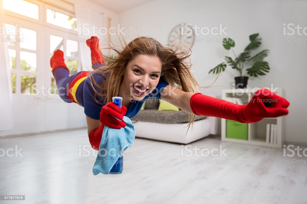 Pretty woman superhero flying through the room with a mop stock photo