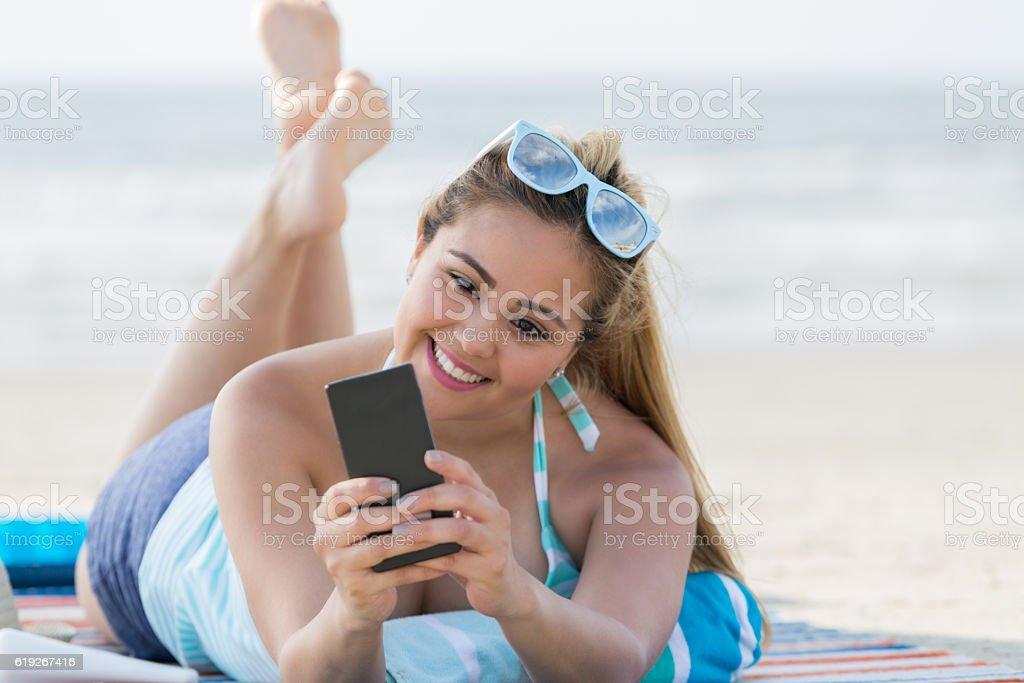 Pretty woman takes selfie on the beach stock photo