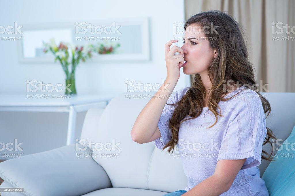 Pretty woman taking her inhaler stock photo