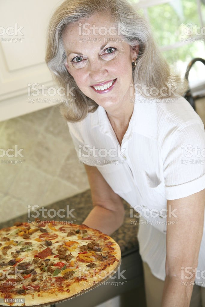 Pretty Woman Taking Pizza Out of the Oven royalty-free stock photo