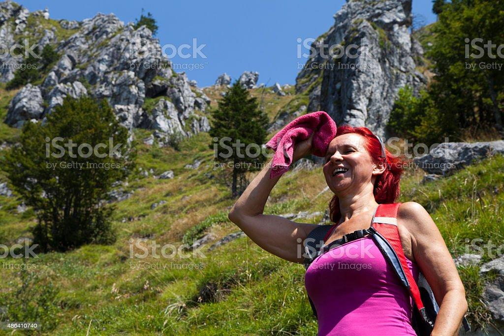 Pretty woman trekker wiping sweat from her forehead stock photo