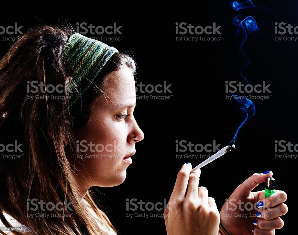 Pretty woman trying marijuana stock photo