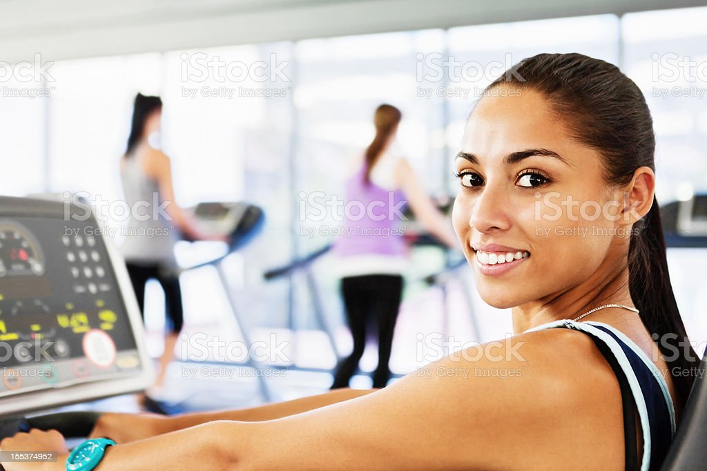 Pretty woman using computerized exercise equipment in gym stock photo