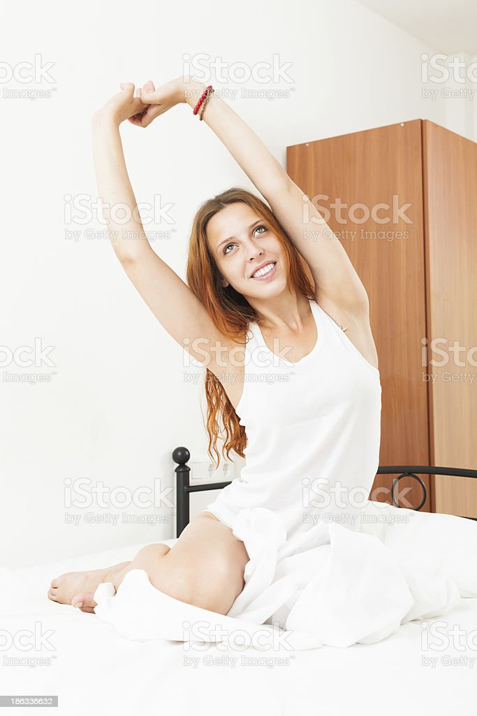 Pretty woman wakes up in her bed royalty-free stock photo