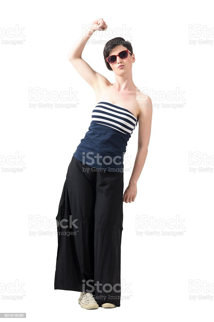 Pretty woman wearing sunglasses with raised arm and clenched fist stock photo