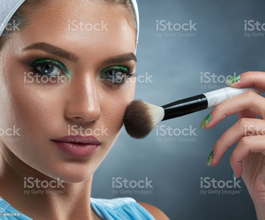 Pretty woman with green makeup drawing blush for herself. stock photo