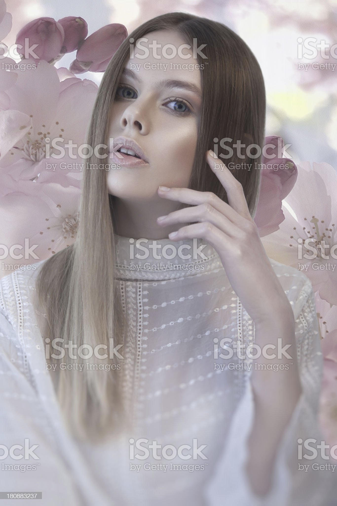 Pretty woman with hand near her face and flower background royalty-free stock photo