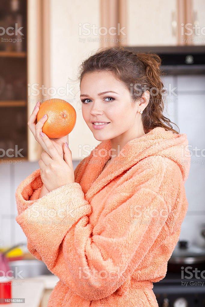Jolie femme avec orange dans la cuisine photo libre de droits