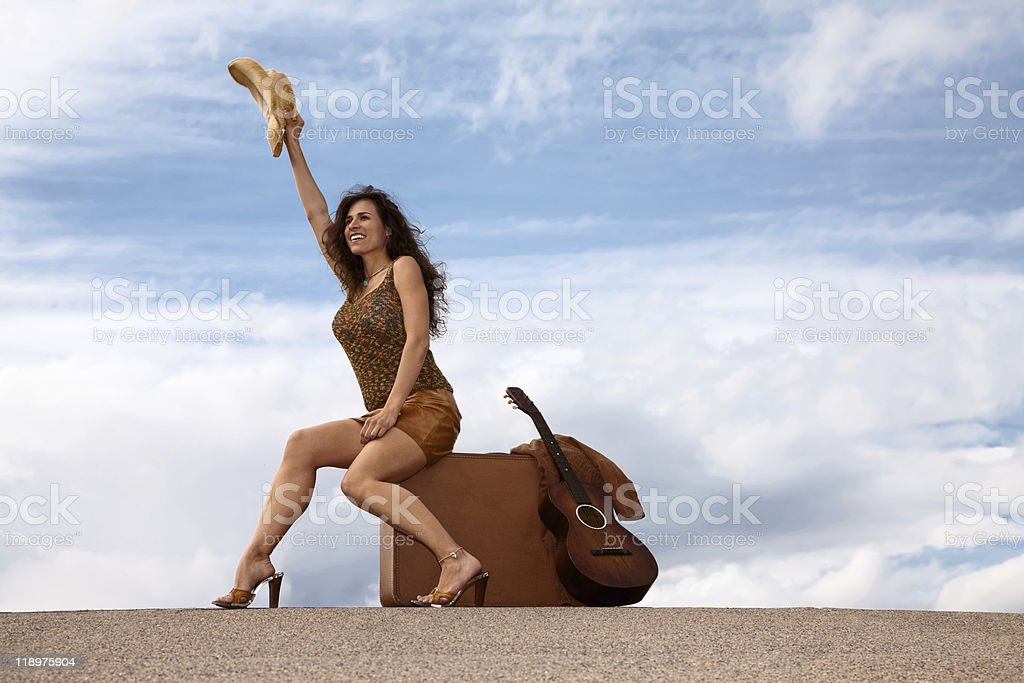 Pretty woman with suitcase and guitar royalty-free stock photo