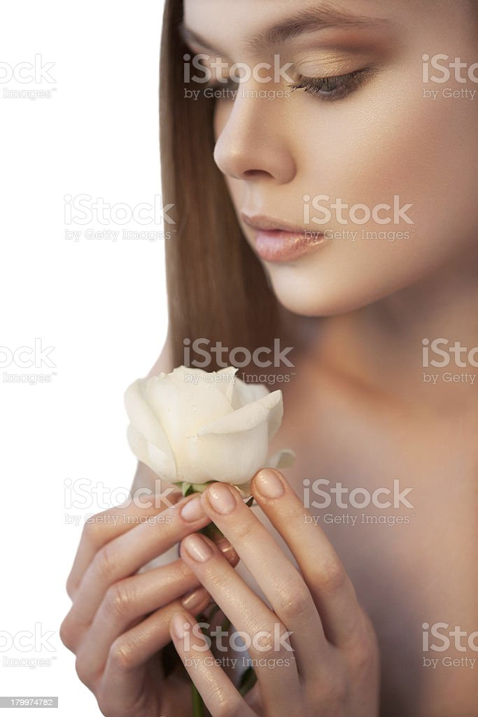 Pretty woman with white rose in her hands looking down royalty-free stock photo