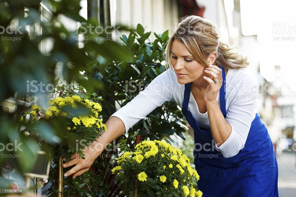 Pretty woman working with flowers and plants at florist royalty-free stock photo