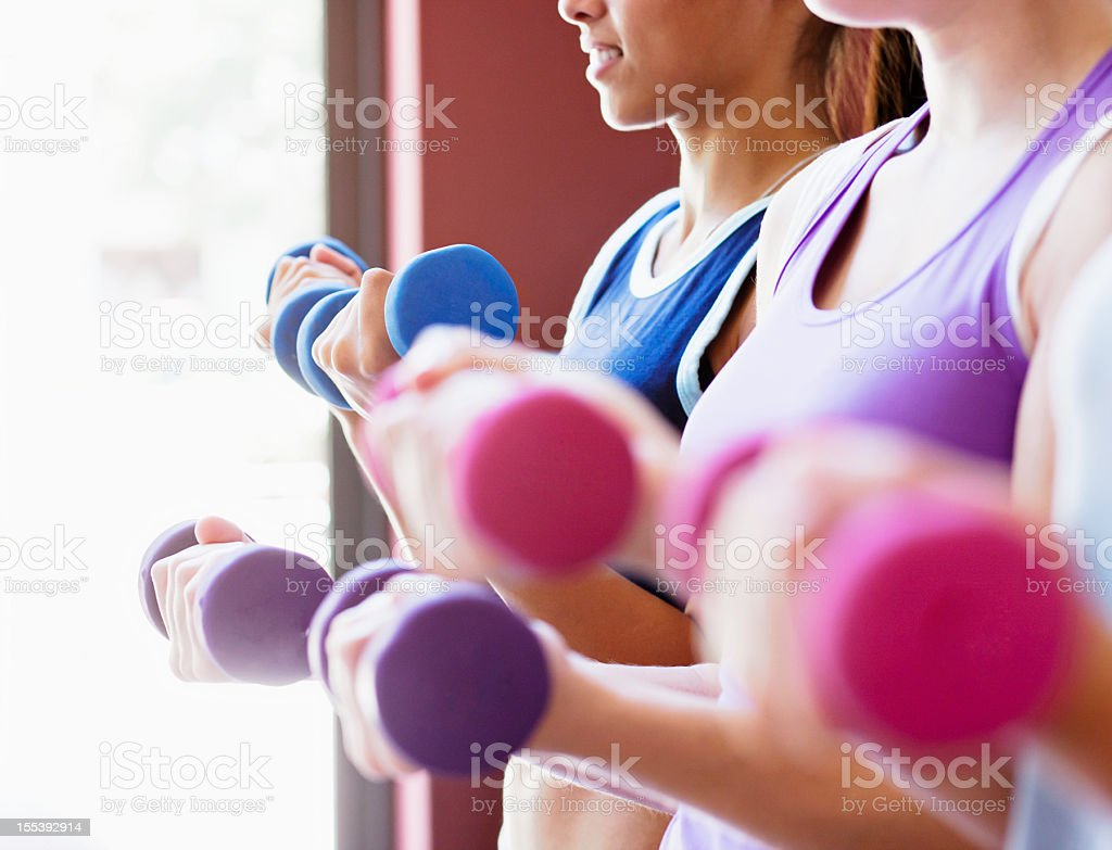 Pretty women lift pastel weights in all-female gym stock photo