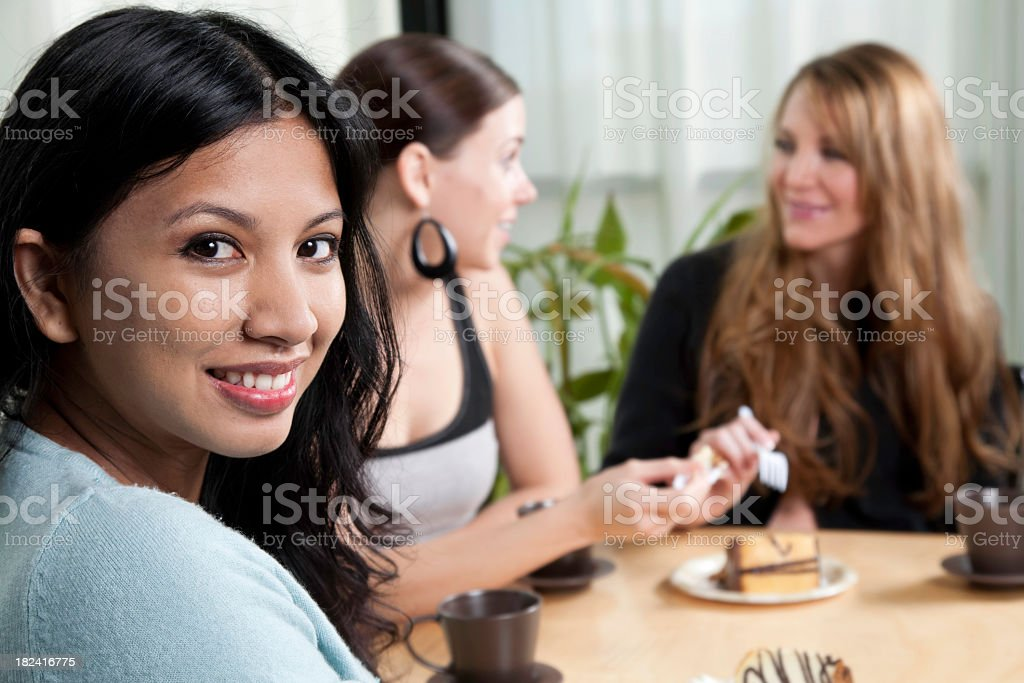 Pretty Women Looking Back and Having Desert with Friends royalty-free stock photo